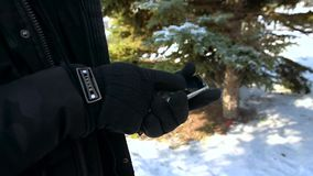 Men`s gloved hands on the background of snow and Christmas trees, hold a touch phone in their hands and try to press it. The conce. Men`s hands in gloves with stock video