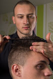 Men's hair cutting with scissors in a beauty salon. Men's hair cutting with comb and scissors in a beauty salon royalty free stock photography