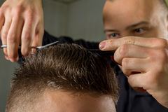 Men's hair cutting with scissors in a beauty salon. Men's hair cutting with comb and scissors in a beauty salon royalty free stock photo