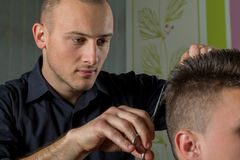Men's hair cutting with scissors in a beauty salon. Men's hair cutting with comb and scissors in a beauty salon stock photos