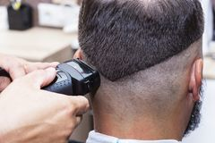 Men`s hair Styling and grooming with the help of scissors machine and hair clippers in the hair salon. Men`s hair Styling and grooming with the help of scissors stock images