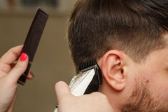 Men`s haircut. Professional hairdresser doing haircut men`s hair. Cutting electric razor. Beauty saloon. Male beauty. The client is a hipster Stock Photo