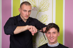 Men's hairstyling and haircutting with hair clipper and scissor stock images