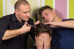 Men's hairstyling and haircutting with hair clipper and scissor. In a barber shop or hair salon stock images