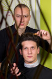 Men's hairstyling and haircutting with hair clipper and scissor. In a barber shop or hair salon stock image