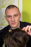 Men's hairstyling and haircutting with hair clipper and scissor. In a barber shop or hair salon stock photography