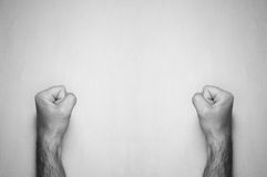 Men`s hairy hands clenched in fists against a gray background Stock Images