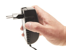 Men's hand with the charger adapter. Cell phone charger in a man's hand. On a white background Stock Image
