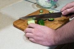 Men`s hand cutting a cucumber. Stock Image