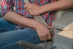 Men`s hand fastens the seat belt of the car. Close your car seat belt while sitting inside the car before driving and take a safe stock images