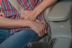 Men`s hand fastens the seat belt of the car. Close your car seat belt while sitting inside the car before driving and take a safe stock photography