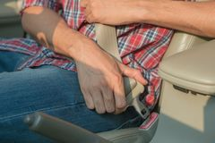 Men`s hand fastens the seat belt of the car. Close your car seat belt while sitting inside the car before driving and take a safe royalty free stock photo