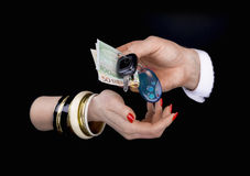 Men's hand giving to  woman's hand eurobanknotes and car keys. Men's hand giving to  woman's hand euro banknotes and car keys  in a black background Royalty Free Stock Image