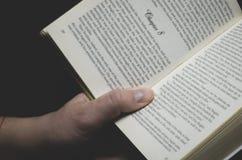 Men& x27; s-Hand hält ein offenes Buch bereit zum Ablesen lizenzfreie stockfotos