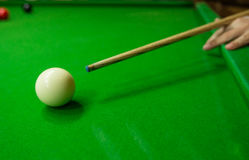 Men`s hand hold Snooker cue with snooker ball on green table background. Men`s hand hold Snooker cue with snooker ball on green table Royalty Free Stock Photo