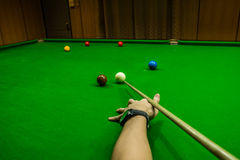 Men`s hand hold Snooker cue with snooker ball on green table background. Men`s hand hold Snooker cue with snooker ball on green table Royalty Free Stock Photos
