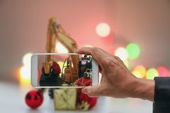 Men `s Hand Holding A Smartphone. Christmas Photography Stock Image