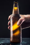 Men`s hand holding a bottle of beer. On a dark background Royalty Free Stock Photo