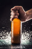 Men`s hand holding a bottle of beer. On a dark background Stock Photography