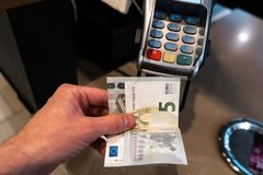 Men`s hand holding EURO banknotes near a payment terminal POS in a cafe stock images