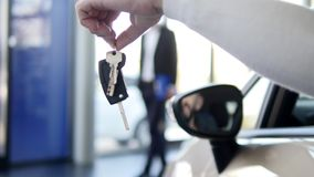 Men`s hand holding a key from the car, symbolize joy purchase transport, crediting, driving.  stock video footage