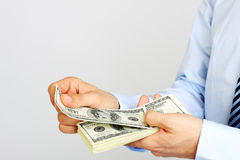 Men's hand holding money american hundred dollar bills. Hand of business man offering money. Royalty Free Stock Image