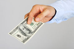 Men's hand holding money american hundred dollar bills. Hand of business man offering money. Stock Photography