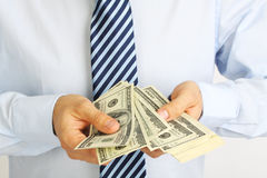 Men's hand holding money american hundred dollar bills. Hand of businessman offering money. Businessman counting money. Royalty Free Stock Images