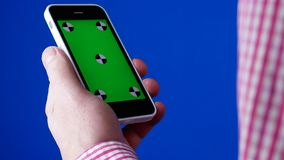 Men`s hand holding the smartphone in a vertical position. Green screen on the phone and blue chromakey. Tracking markers. Ads concept and template royalty free stock photos
