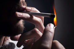 Men's hand lights cigarette with a match Royalty Free Stock Image