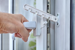 Men`s hand opens a plastic window with stop turning. Royalty Free Stock Photos