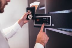 Men`s hand opens a safe hidden in the wardrobe. Small home or hotel safe stock photography