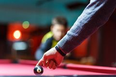 Men`s hand points on ball in billiard or pool club. Boy with billiard cue strikes the ball on table. Active Leisure, sport royalty free stock photography