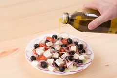 Men`s hand pouring olive oil into Greek salad. Wooden background stock images