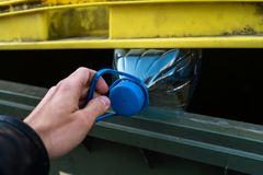 Men`s hand throwing out a plastic bottle in a yellow green trash bin - Recycle for nature stock image