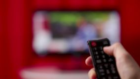 Men`s hand with TV remote TV channel switching. Hand Hold Tv Remote Control. Tv On The Background stock video