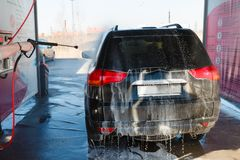 Men's hand wash dirty SUV by high pressure wash. Touchless car wash self-service in the open air. Contactless car wash self-servi. Ce. Young man washing his car Stock Images