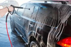 Men's hand wash dirty SUV by high pressure wash. Touchless car wash self-service in the open air. Contactless car wash self-servi. Ce. Young man washing his car Royalty Free Stock Images