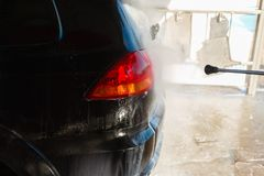 Men's hand wash dirty SUV by high pressure wash. Touchless car wash self-service in the open air. Contactless car wash self-servi. Ce. Young man washing his car Royalty Free Stock Image