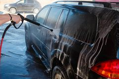 Men's hand wash dirty SUV by high pressure wash. Touchless car wash self-service in the open air. Contactless car wash self-servi. Ce. Young man washing his car Stock Photo