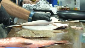 Men`s hands in black gloves are cutting fish stock video footage