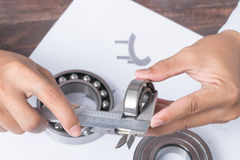 Men's hands with a caliper and bearings. Job Engineer developer. Of automotive parts stock photography