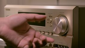 Men`s hands are changing the volume in the amplifier. Of the home theater stock video footage