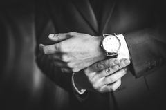 Men`s hands with the clock. Black and white image of man in suit with clock Royalty Free Stock Image