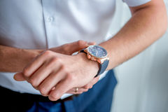 Men`s hands with a clock. Businessman clock clothes, businessman checking time on his wristwatch. men`s hand with a watch, watch on a man`s hand, putting the Stock Photos