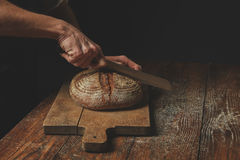 Men`s hands cut bread Royalty Free Stock Photos