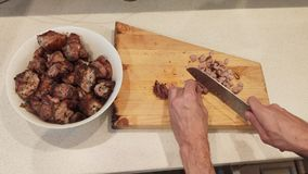Men`s hands cut the finished steak into small pieces. grilling meat.  stock video