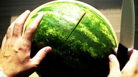 Men`s hands cut watermelon. Slices of ripe red watermelon. Beautiful delicious, juicy sliced watermelon, on the table, colorful. Ripe fruit, natural product stock footage