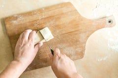 Men`s hands cutting raw dough Stock Images