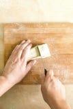 Men`s hands cutting raw dough Royalty Free Stock Photos